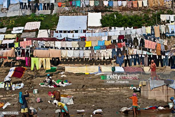 Washermen and women washing laundry with their hands and drying clothes at the Dhobi Ghat on the banks of River Ganges the most sacred river of...