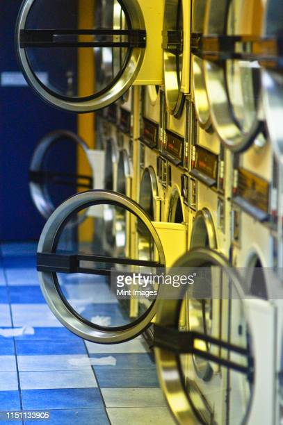 washers and dryers in public laundromat - launderette stock pictures, royalty-free photos & images