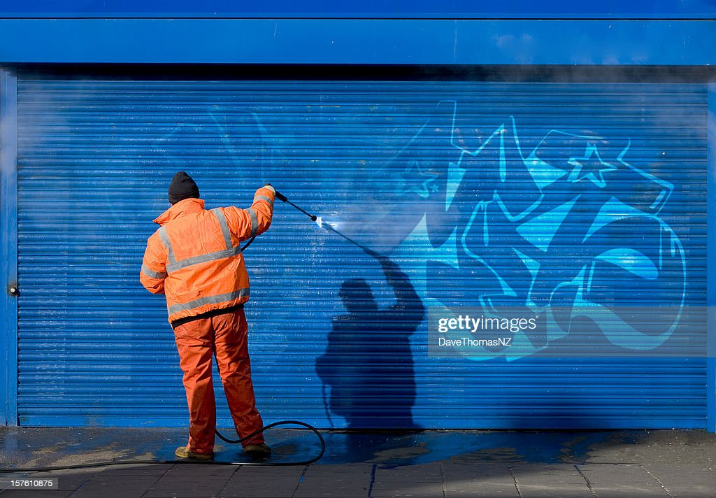 Washing graffiti off a security grill. : Stock Photo