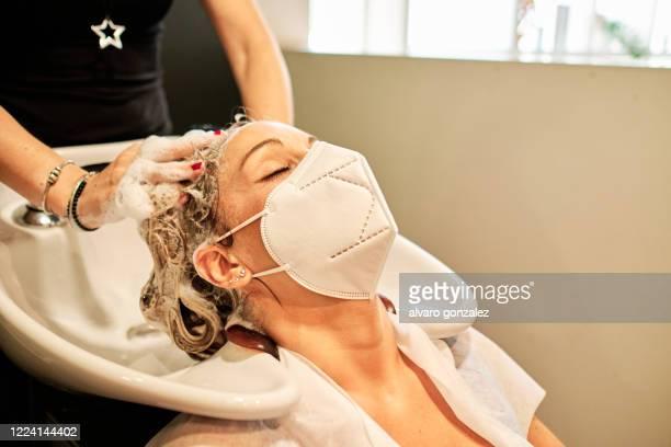 washing hair in hair salon using protective face mask during coronavirus outbreak - friseur stock-fotos und bilder