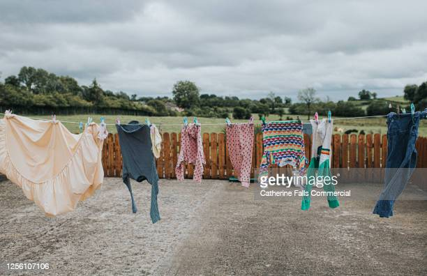 washing hanging on a washing line in a paved back yard - wind stock pictures, royalty-free photos & images