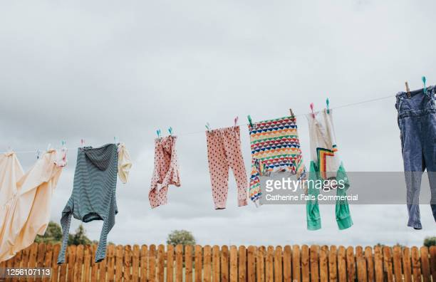 washing hanging on a washing line in a paved back yard - laundry stock pictures, royalty-free photos & images
