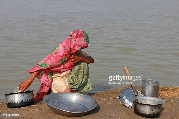 washing kitchen utensil. - pakistani culture stock photos and pictures