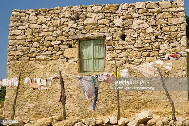 washing line in front of an old stone wall with small window at kastri on gavdos, greece, europe - gavdos stock pictures, royalty-free photos & images