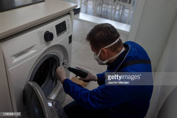 washing machine repair technician during pandemic - washing machine stock pictures, royalty-free photos & images