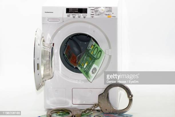 washing machine with paper currencies and handcuffs against white background - money laundering stock pictures, royalty-free photos & images