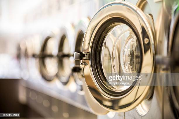 washing machines - clothes washer's door in a public launderette - laundry stock pictures, royalty-free photos & images