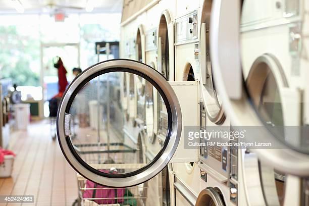 Washing machines with doors open in lauderette