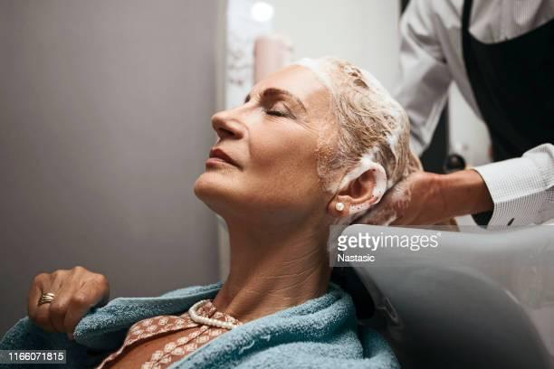 lavage des cheveux matures de femme - cheveux gris photos et images de collection