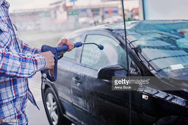 washing the car with a water sprayer. debica, poland - car wash brush stock photos and pictures