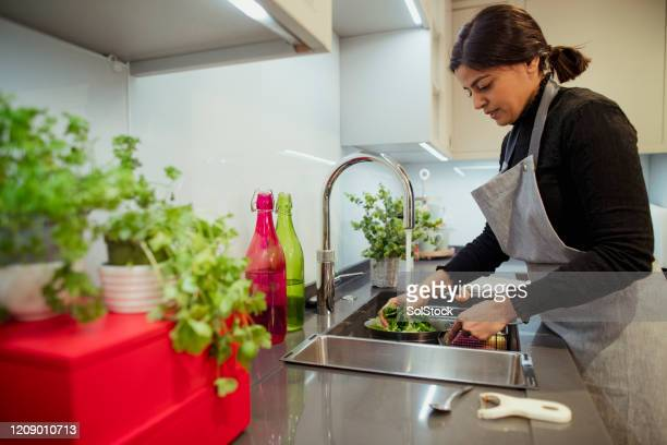 washing the veggies - femalefocuscollection stock pictures, royalty-free photos & images