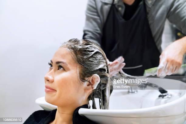 美容室で紫シャンプーで女性の髪を洗う - 漂白した ストックフォトと画像