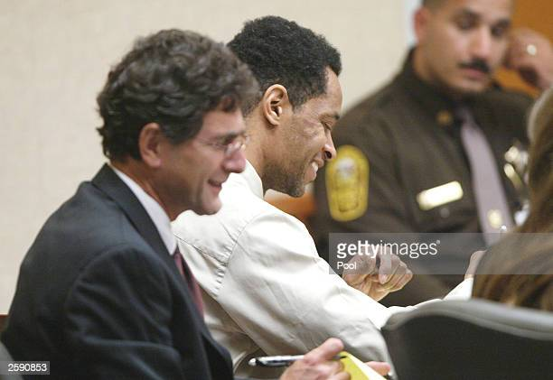 Washington area sniper suspect John Allen Muhammad laughs with his attorney Jonathan Shapiro after a break in his trial at the Virginia Beach Circuit...