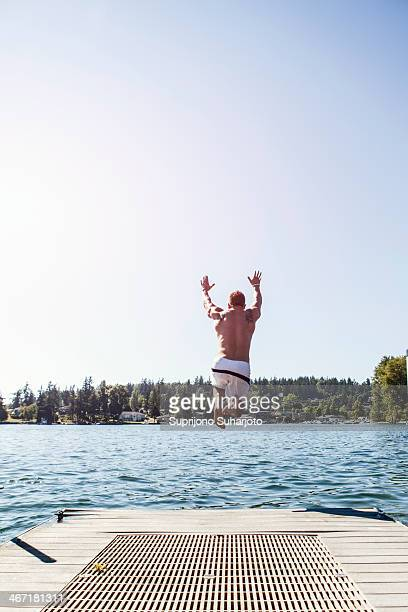 USA, Washington, Bellingham, Young man jumping to lake from jetty