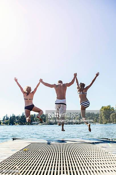USA, Washington, Bellingham, Young people jumping to lake from jetty