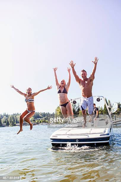 USA, Washington, Bellingham, Young people jumping to lake from motorboat