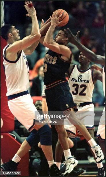 Washington Bullets George Muresan blocks a shot by Denver Nuggets Dale Ellis as the Bullets' Jaren Jackson looks on in the fourth quarter in Landover...