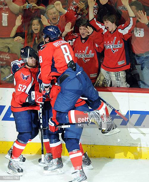 Washington Capitals' Alex Ovechkin jumps on top of his teammates as the Capitals celebrates a goal by John Carlson late in the third period to tie...