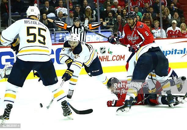Washington Capitals center Evgeny Kuznetsov checked to the ice as Buffalo Sabres defenseman Brendan Guhle pokes the puck away during a NHL game on...