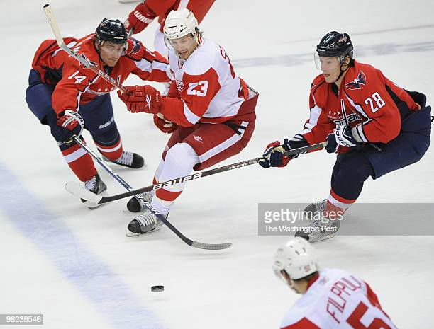 Washington Capitals center Tomas Fleischmann left and Washington Capitals left wing Alexander Semin right try to steal the puck as Detroit Red Wings...