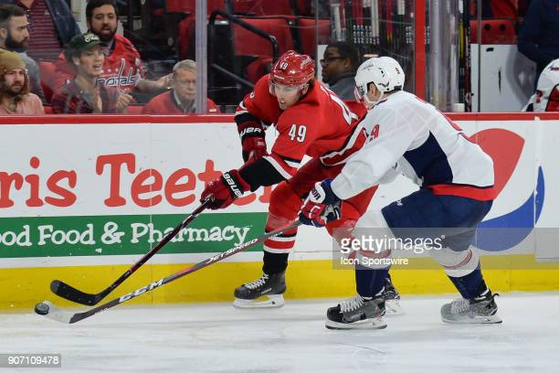 Washington Capitals Defenceman Dmitry Orlov and Carolina Hurricanes Center Victor Rask fight for a puck along the boards during a game between the...