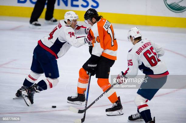 Washington Capitals Defenceman John Carlson pushes Philadelphia Flyers Center Sean Couturier off of the puck in the third period during the game...