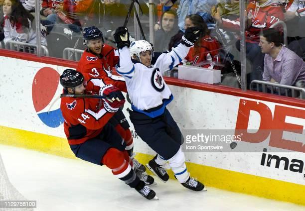 Washington Capitals defenseman Brooks Orpik and defenseman Nick Jensen get tangled up with Winnipeg Jets left wing Brandon Tanev on March 10 at the...