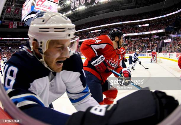 Washington Capitals defenseman Brooks Orpik hits Winnipeg Jets center Bryan Little in the first period on March 10 at the Capital One Arena in...