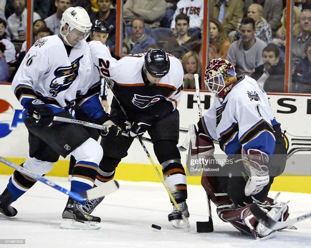 Washington Capitals defenseman Shaone Morrisonn (26) ties up Philadelphia Flyers center R.J. Umberger (20) while Capitals goalie Brent Johnson (1) looks for the save on Thursday, November 3, 2005 in Philadelphia, PA. The Philadelphia Flyers defeated the Washington Capitals 8-1.