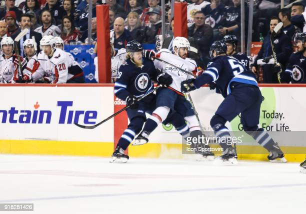 Washington Capitals forward Chandler Stephenson is bodied by Winnipeg Jets defenseman Tyler Myers and Winnipeg Jets forward Patrik Laine during the...