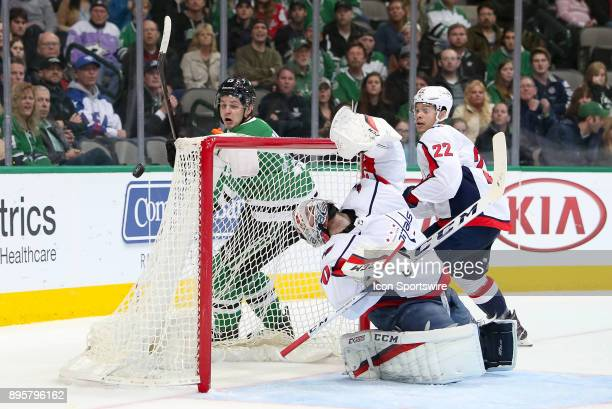 Washington Capitals goalie Braden Holtby contorts himself while following a deflected puck during the hockey game between the Washington Capitals and...