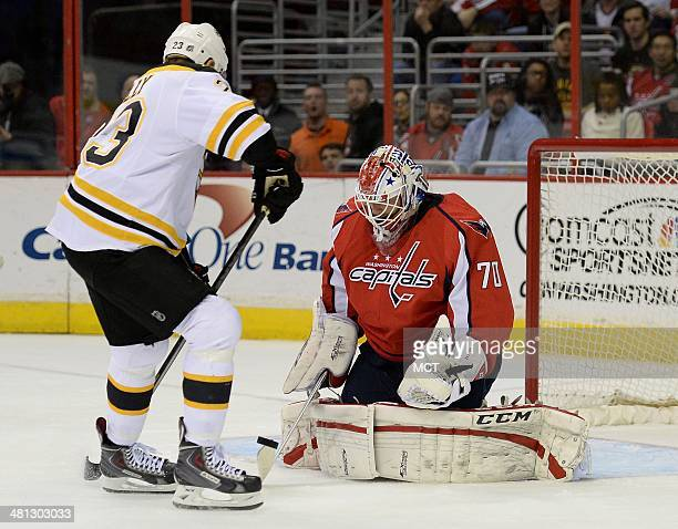 Washington Capitals goalie Braden Holtby makes a save as Boston Bruins center Chris Kelly looks for a rebound in the first period at the Verizon...