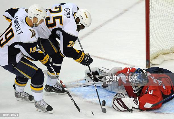 Washington Capitals goalie Michal Neuvirth right makes a save against Buffalo Sabres' Tim Connolly and Michael Grier during thirdperiod action center...