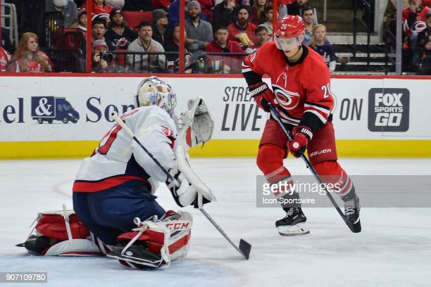 Washington Capitals Goalie Philipp Grubauer catches a puck in front of Carolina Hurricanes Left Wing Sebastian Aho during a game between the...