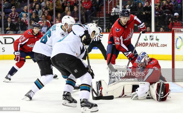 Washington Capitals goalie Philipp Grubauer smothers the puck as San Jose Sharks left wing Marcus Sorensen and right wing Jannik Hansen move in...