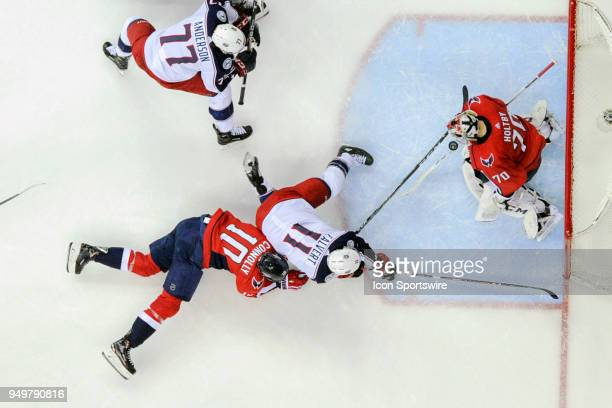Washington Capitals goaltender Braden Holtby makes a save on a third period shot by Columbus Blue Jackets left wing Matt Calvert who is taken to the...