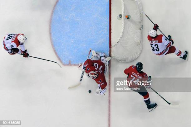 Washington Capitals goaltender Braden Holtby makes a save on shot by Carolina Hurricanes left wing Jeff Skinner as left wing Teuvo Teravainen skates...