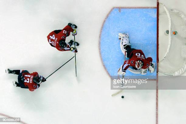 Washington Capitals goaltender Braden Holtby makes a save with the help of left wing Jakub Vrana and right wing Tom Wilson against the Carolina...