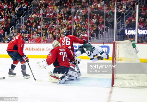 Washington Capitals goaltender Braden Holtby makes a third period save on a shot by Minnesota Wild center Ryan Donato who is hit by center Nic Dowd...