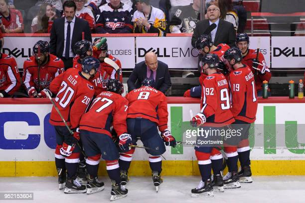 Washington Capitals head coach Barry Trotz looks up at the clock during a time out in the third period as Assistant Coach Blaine Forsythe meets with...