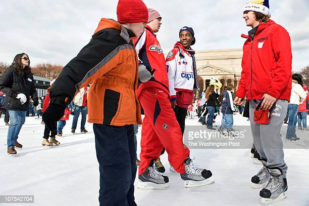 Washington Capitals hockey player Marcus Johansson center momentarily looses his balance as he skates with Brian O'Daniel of Dunkirk Md left and...