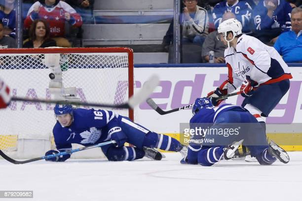 TORONTO ON NOVEMBER 25 Washington Capitals left wing Alex Ovechkin chips the puck over Toronto Maple Leafs center Mitchell Marner and Toronto Maple...