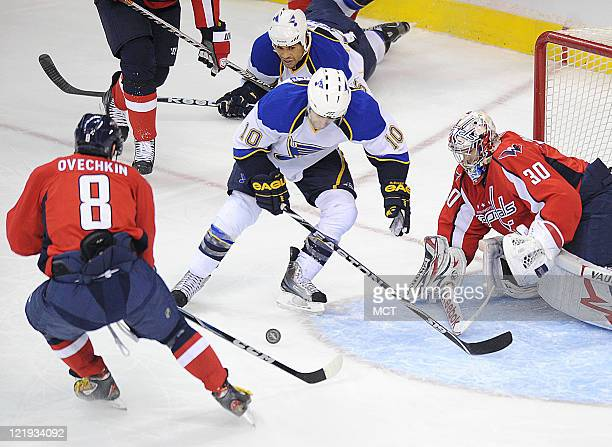 Washington Capitals left wing Alex Ovechkin clears the puck as St Louis Blues center Andy McDonald tries to get a shot off against Capitals goalie...