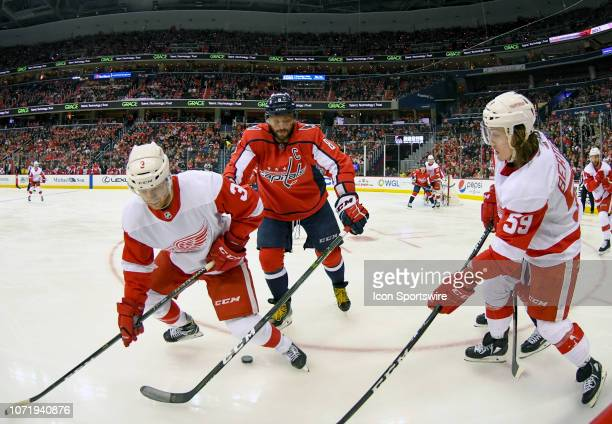 Washington Capitals left wing Alex Ovechkin fights for a loose puck in the second period against Detroit Red Wings defenseman Nick Jensen and left...