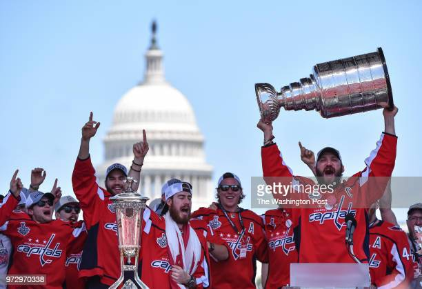 Washington Capitals left wing Alex Ovechkin hoists the Stanley Cup alongside his teammates during the victory parade and rally on the National Mall...