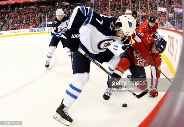 Washington Capitals left wing Andre Burakovsky goes to the ice against Winnipeg Jets defenseman Ben Chiarot on March 10 at the Capital One Arena in...