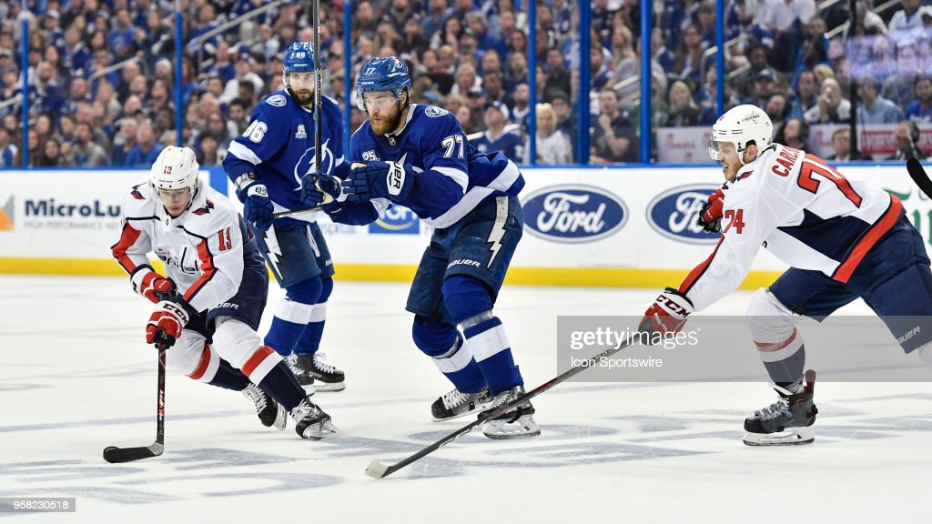 Washington Capitals left wing Jakub Vrana (13) takes the puck while Tampa Bay Lightning defender Victor Hedman (77) and Washington Capitals defender John Carlson (74) battle for the puck during the second period of the second game of the NHL Stanley Cup Eastern Conference Final between the Washington Capitals and the Tampa Bay Lightning on May 13, 2018, at Amalie Arena in Tampa, FL.