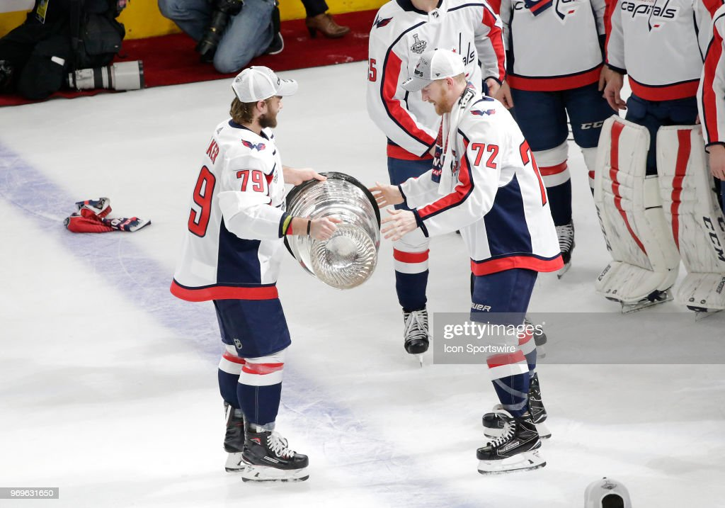 Washington Capitals left wing Nathan Walker (79) hands the Stanley Cup to Washington Capitals center Travis Boyd (72) after defeating the Vegas Golden Knights 4-3 in Game Five of the 2018 NHL Stanley Cup Final at T-Mobile Arena on June 7, 2018 in Las Vegas, Nevada.