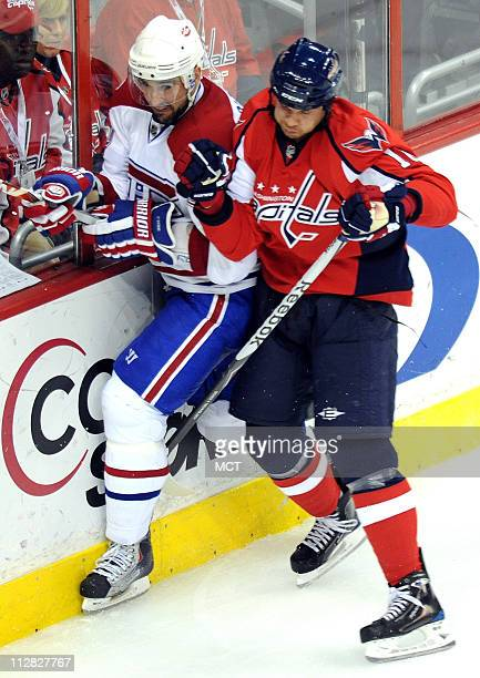 Washington Capitals' Matt Bradley checks Montreal Canadiens' Ryan O'Byrne into the wall during the 3rd period of Game 5 in the NHL Eastern Conference...
