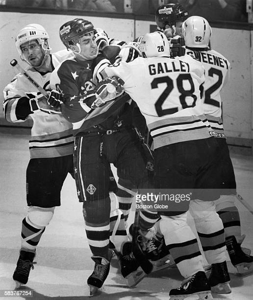 Washington Capitals player Geoff Courtnall center battles Boston Bruins player Bob Carpenter left Garry Galley middle and Don Sweeney in front of the...